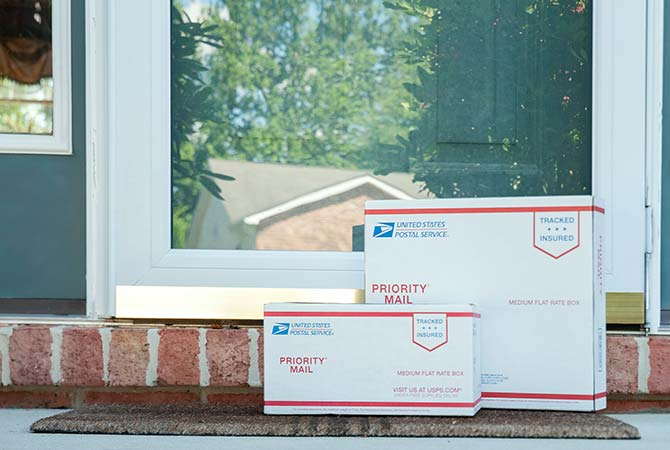 Priority Mail packages sitting on a front doorstep mat for USPS pickup.